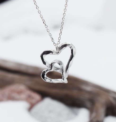silverhalsband i form av ett dubbelhjärta hängande i luften utomhus