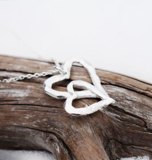 silverhalsband i form av ett dubbelhjärta på trädgren utomhus