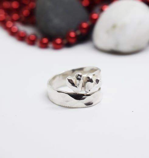 silverring med hjärta på vit botten med stenar och röda kulor bakom
