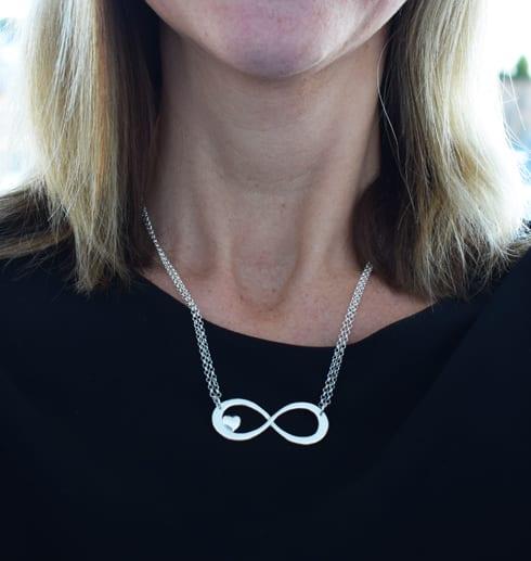 silverhalsband i form av en evighetssymbol runt en hals som en människa