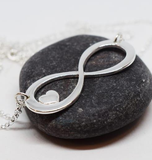 Halsband i form av en evighetssymbol på en mörkgrå sten med vit bakgrund