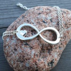 evighetssymbol i silver i form av ett armband på en röd sten
