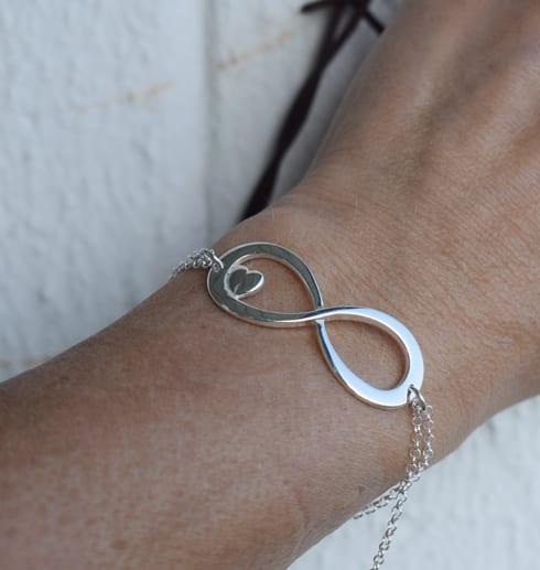 evighetssymbol i silver på handled