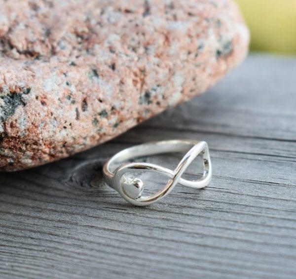 evighetssymbol i form av en ring på trä med en röd sten på bilden