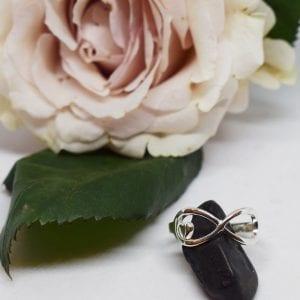evighetssymbol i form av en silverring på en svart sten med en ros i bakgrunden
