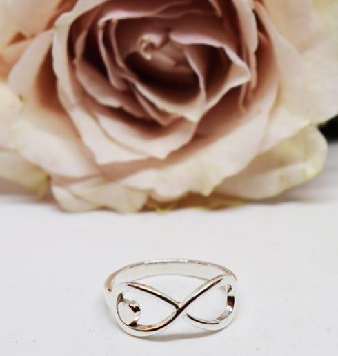 ring i silver med evighetssymbolen på vid botten med en rosa ros