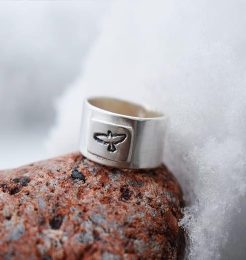 silverring med stansad fågel på röd sten med snö bakom