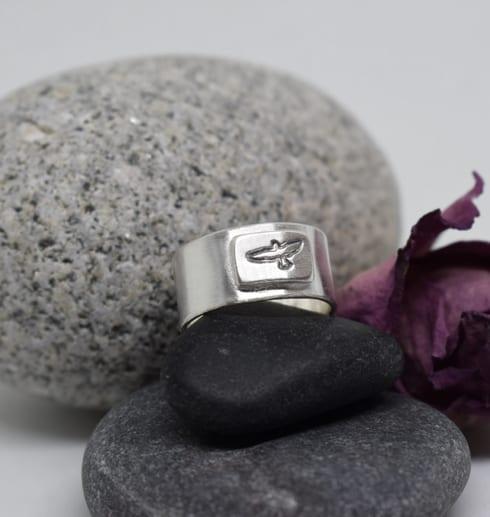silverring med fågel stansad på stenar med lila ros