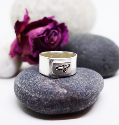 silverring med fågel på sten med lila ros bakom