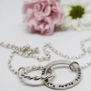 silverhalsband motvit botten och rosa och vit blomma bakom
