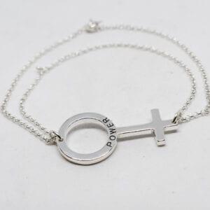 silverarmband med kvinnosymbolen på vit bakgrund