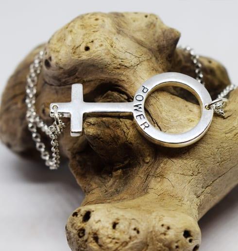 silverarmband med kvinnosymbolen som ligger över en trädgren