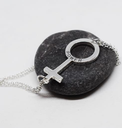 silverarmband med kvinnosymbolen som ligger över en mörkgrå sten