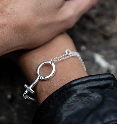 silverarmband med kvinnomärket kring handled med svart skinnjacka