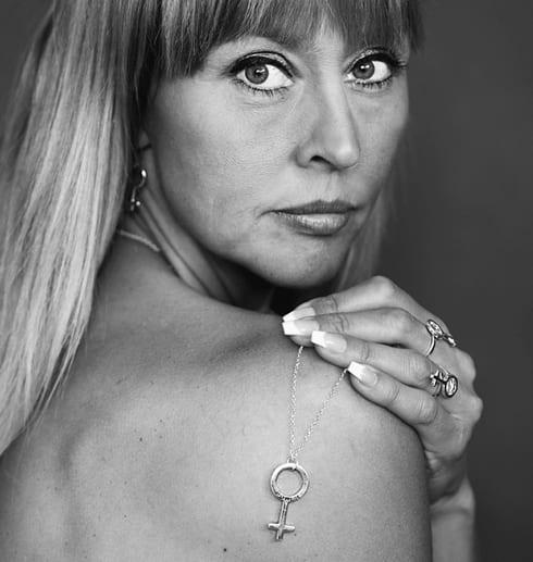 kvinna med silverhalsband i form av ett kvinnomärke över axeln