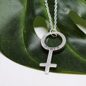 silverhalsband i form av kvinnosymbolen på grönt blad