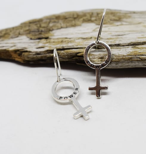 örhängen i silver i form av kvinnosymbolen mot en träbit