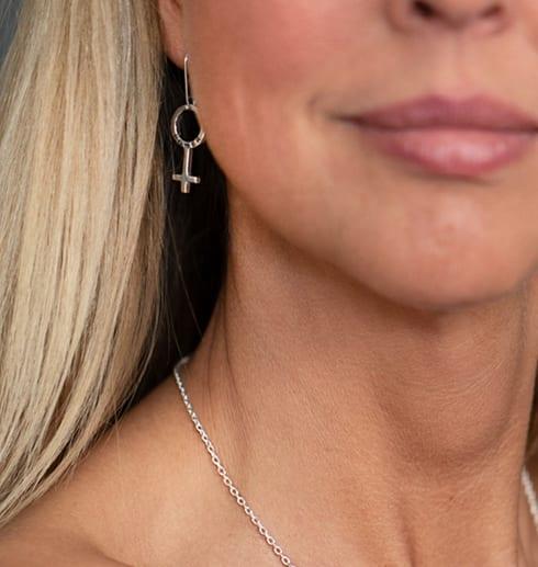 kvinnoansikte med silverörhänge i form av en kvinnosymbol i örat