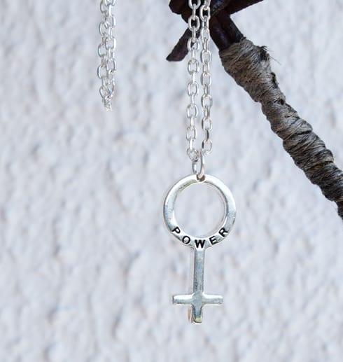 kvinnosymbol i silver som hänger på en taggtråd