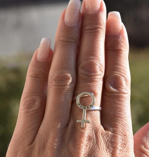 hand med silverring md kvinnosymbol utomhus