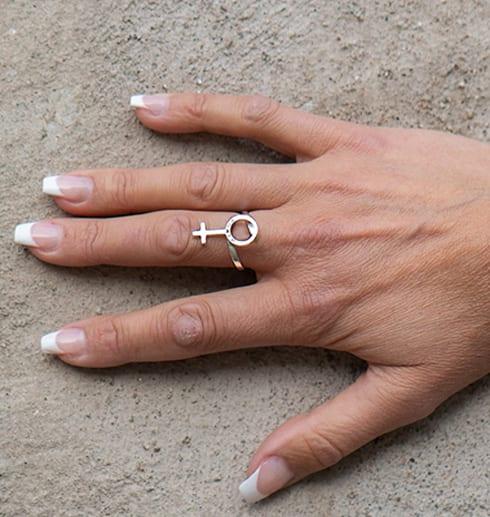 hand med silverring i form av kvinnosymbol mot gråbrun bakgrund