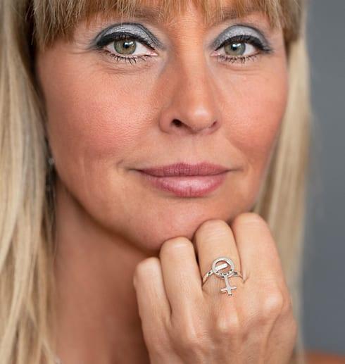 kvinnoansikte med en silverring på ett finger framför