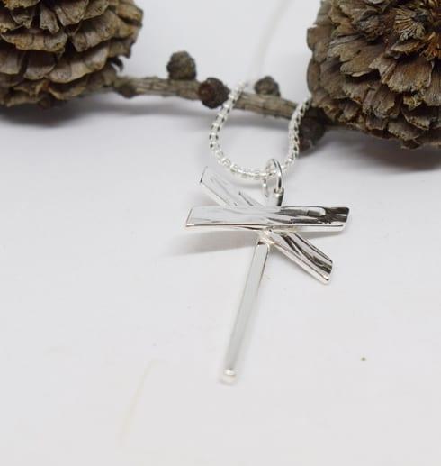 ledkrysshalsband i silver på vit bottenmed kottar bakom