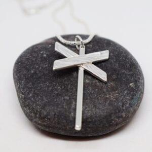 silverhalsband i form av ett ledkryss i kedja på mörkgrå sten