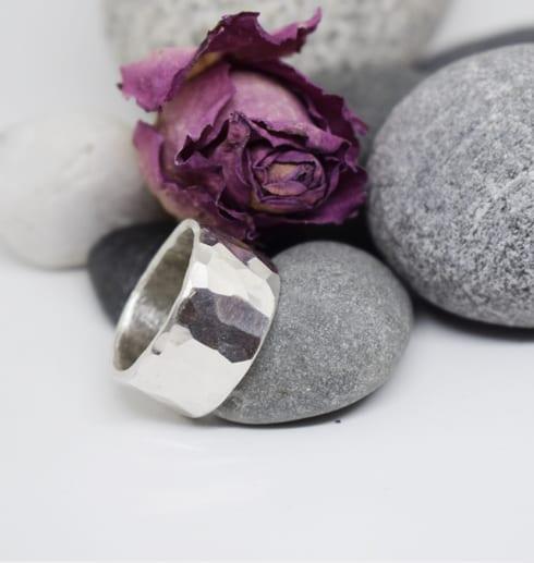 hamrad silverring på stenar och ros
