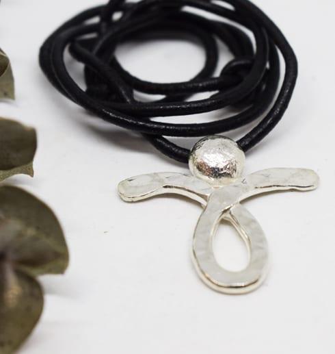 silverängel med läderband med grön kvist bredvid