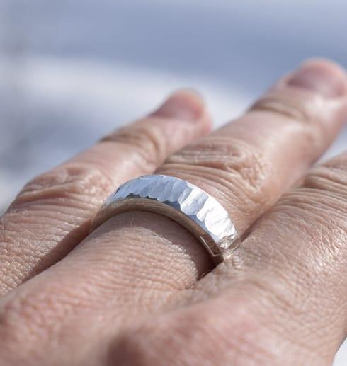 hamrad silverring på finger utomhus