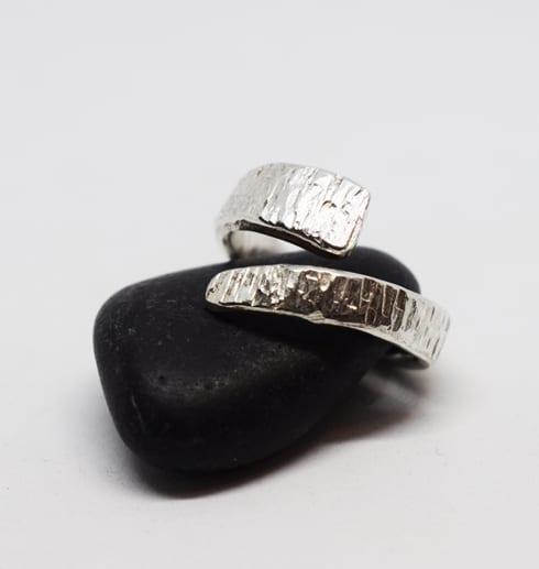 hamrad omlottring i silver på svart sten