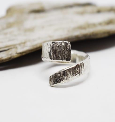 hamrad omlottring i silver på vit bakgrund med träbit bakom