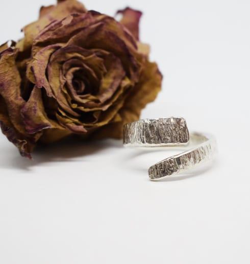 hamrad omlottring i silver på vit bakgrund med brun ros bredvid