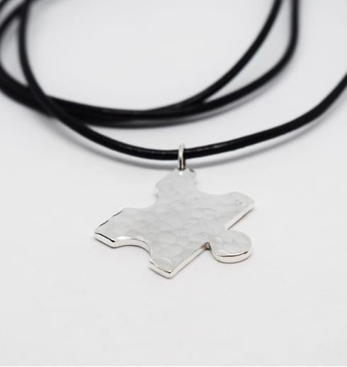 hamrad pusselbit i silver hängande i en svart läderrem med vit bakgrund