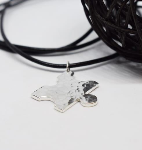 pusselbit i silver i ställbar läderrem på vit bakgrund med svart trådboll på sidan