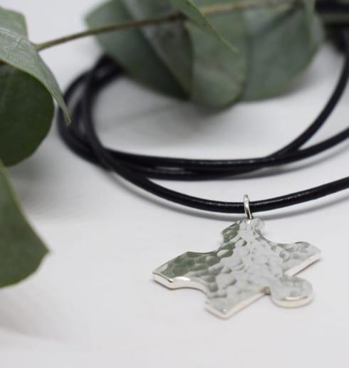 pusselbit i silver i ställbar läderrem på vit bakgrund med gröna löv bakom