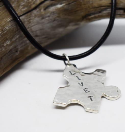 pusselbit i silver med texten LIVET i läderrem på vit bakgrund med trädgren bakom