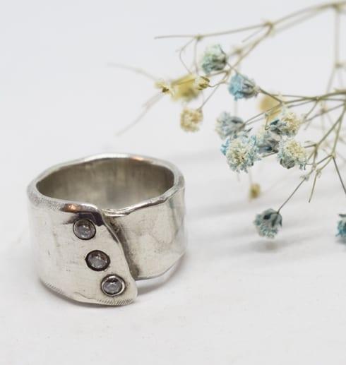 silverringmed stenar på vit botten med blå och gula blommor bredvid
