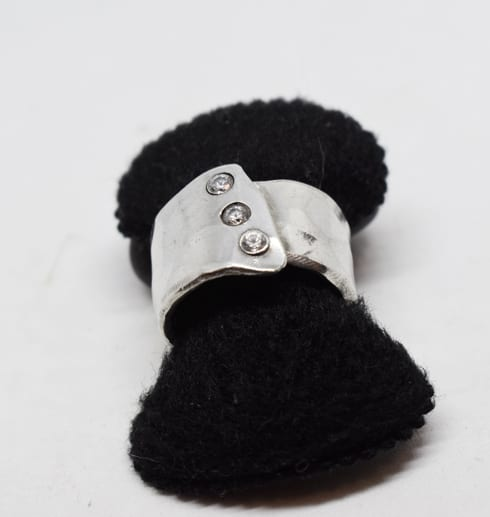 silverring med tre stenar på svart sammet