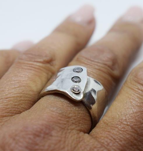 silverring med tre stenar på finger