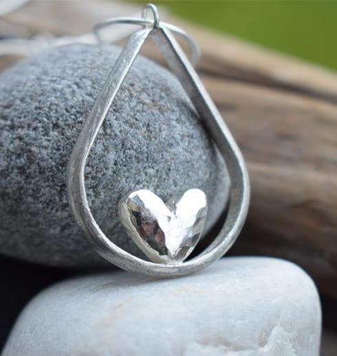 droppformat silverhalsband med hjärta i mitten på stenar utomhus
