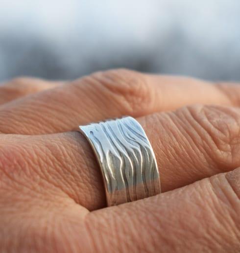 bred ring med mönster på finger