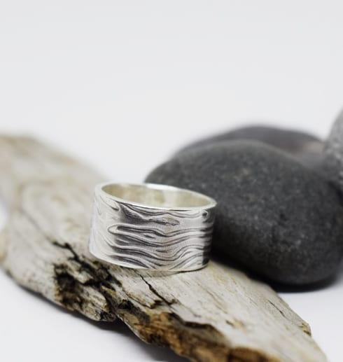 silverring med mönster på trä med stenar bakom
