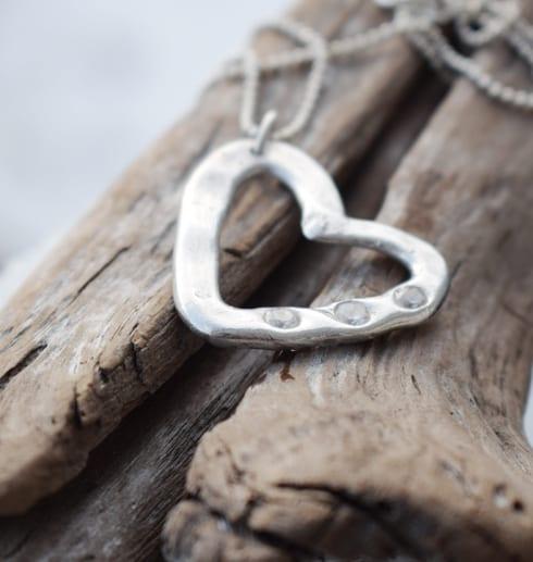 silverhalsband i form av ett hjärta med stenar på träbit utomhus