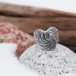 silverring med mösntrat hjärta på stenar med trä och snö utomhus