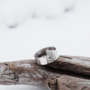 silverring med utsågat hjärta på trä utomhus