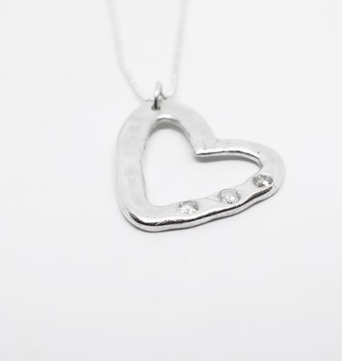 silverhjärta med stenar på vit bakgrund