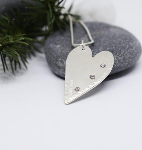 silverhjärta med stenar på grå sten med grankvist