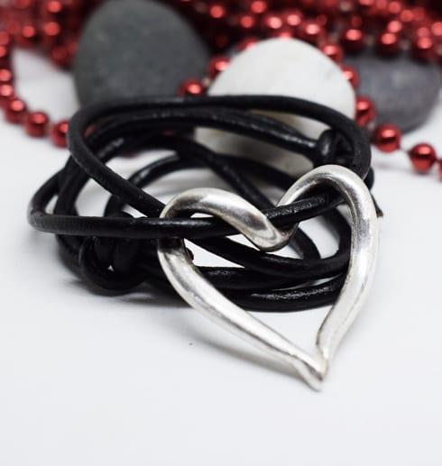 silverhjärta i läderrem med stenar och röda kulor bakom